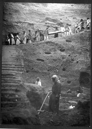 Workers carry the complete skeleton on its board up 50 feet of carved stairs and out of Pit F.